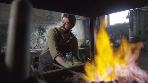 Blacksmith Standing at Furnace