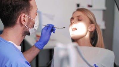 Dentist using dental drill and dental mirror