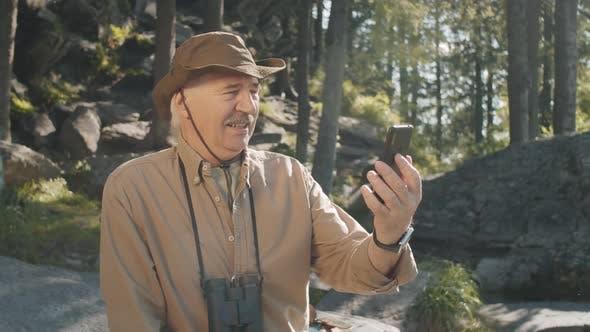 Elderly Male Hiker Video Calling on Smartphone