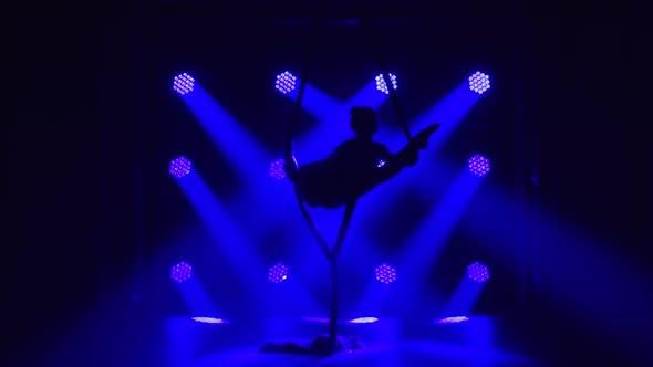 Female Aerial Equilibrium Gymnast Performing Balancing on a Air Silk in a Dark Studio with Blue