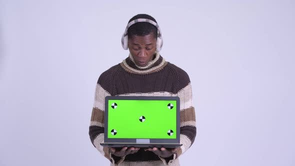 Thumbnail for Young Happy African Man Showing Laptop and Looking Surprised Ready for Winter