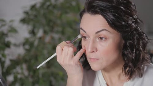 Applying the Morning's Makeup. The Brunette Creates a Face Drawing for Herself