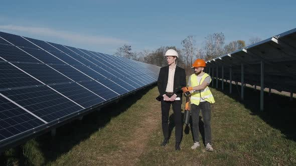 Thumbnail for A Businessman and a Worker Are Walking on the Solar Power Station