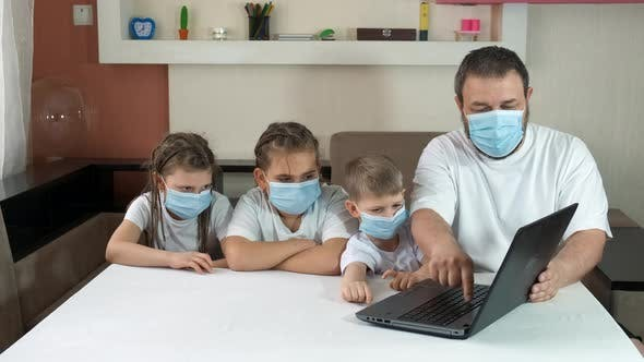 Dad Teaches Children How to Use a Laptop Indoors