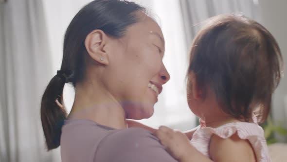 Affectionate Asian Mom Cuddling Baby Girl