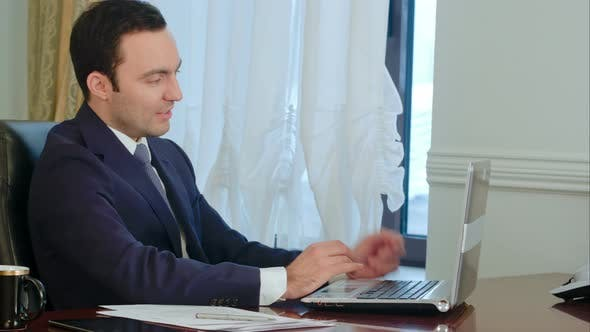 Thumbnail for Smiling Businessman in the Office on Video Conference