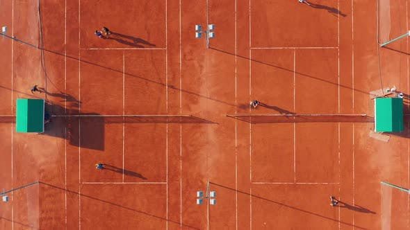 Thumbnail for Aerial Top View of Unrecognizable Tennis Players Playing Tennis on the Orange Court on a Sunny