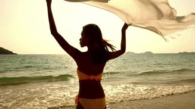 Beautiful young woman with fabric standing on the beach at sunset