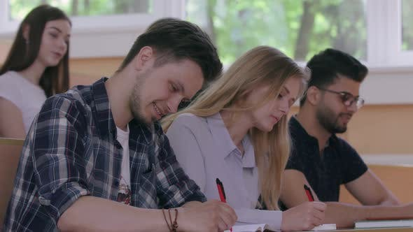 Groupmates Talking, Writing in Copybooks in University