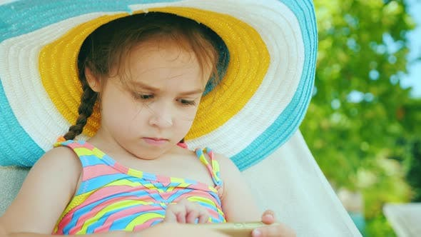 Thumbnail for Cute Girl in a Hat Plays on a Smartphone. Resting After Swimming in the Pool