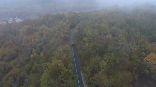 Red Bus Driving on Misty Road in the Forest. Drone Following Truck at Forest Road