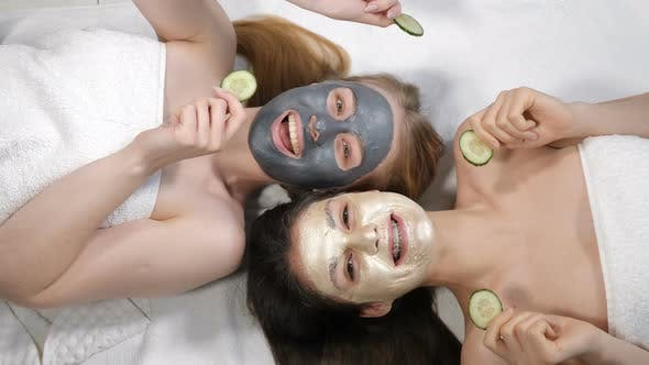 Smiling Female Bst Friends Having Fun with Sliced Cucumber While Applying Clay Face Mask, Isolated
