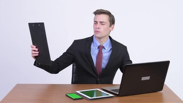 Thumbnail for Young Handsome Businessman Multi-tasking Work Against Wooden Table