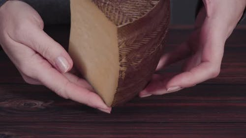 Large wedge of Manchego cheese on a rustic wood background.