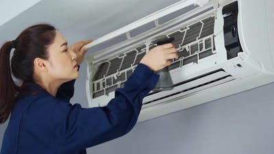 female technician service cleaning the air conditioner indoors