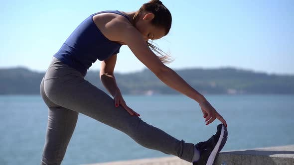 Thumbnail for Sporty Young Woman Stretching Leg at Riverside