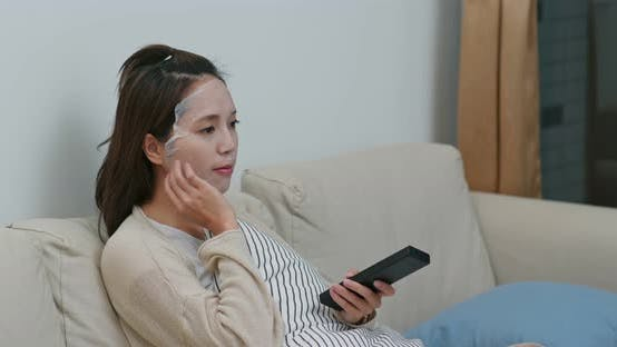Thumbnail for Woman apply face mask in watch TV at home
