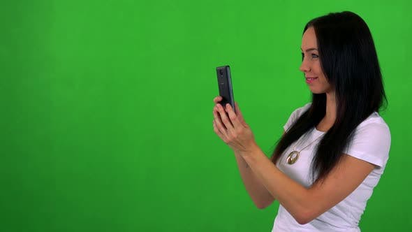 Thumbnail for Young Pretty Woman Takes Photos Wirh Smartphone - Green Screen - Studio