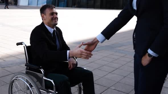 Thumbnail for Businesswoman Shaking Hands with Disabled Businessman Outdoor