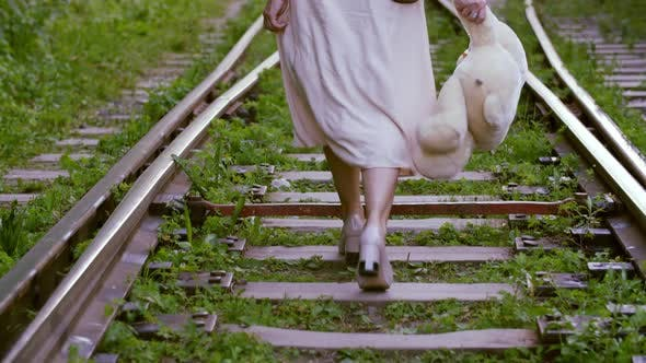 Thumbnail for Female Feet in Shoes High Heels Walking on Railway with Teddy Bear in Hand. Woman Stepping in Sexy