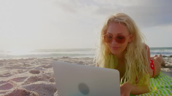 Thumbnail for Woman in bikini and sunglasses using laptop on beach 4k