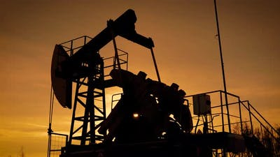 Moving Large Pumpjack Is Pumping Petroleum From Ground in Sunset Time, View Against Orange Sky