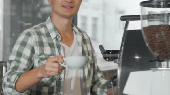 Thumbnail for Glückliche männliche barista lächelnd halten aus Tasse lecker Kaffee an die Kamera