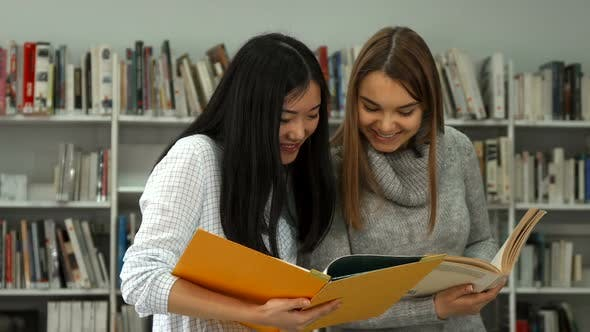 Thumbnail for Two Female Students Compare Information in Two Books at the Library