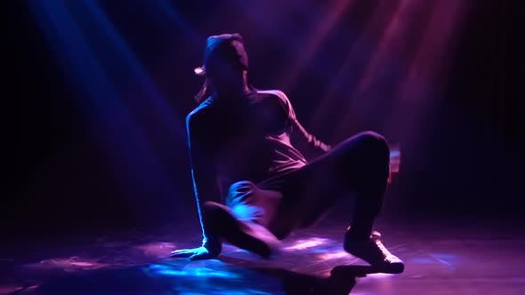 Thumbnail for A Silhouette of a Professional Breakdance and Hip-hop Dancer Rotates on the Floor in the Spotlight