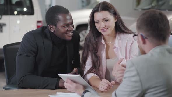 Cover Image for Back View of Young Caucasian Car Dealer Showing Automobiles on His Tablet To Young Multiracial