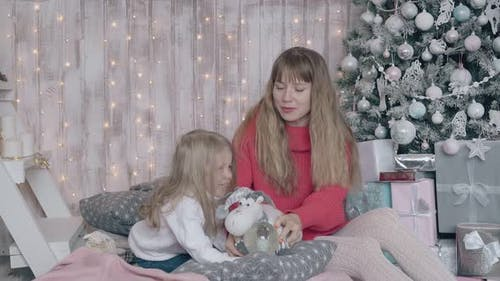Mum Sits on Bed with Daughter and Entertains Little Girl