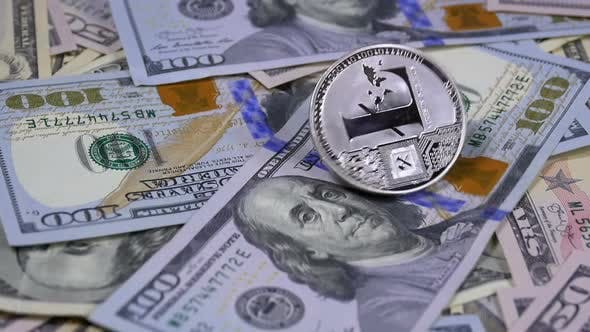 Thumbnail for Silver Litecoin Coin LTC Rotate, Twist, Swirling, Spinning and Falls on the Table with Dollars. Slow