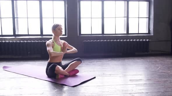 Sporty young woman practicing yoga, sitting in Half Lotus exercise, Siddhasana pose, indoor