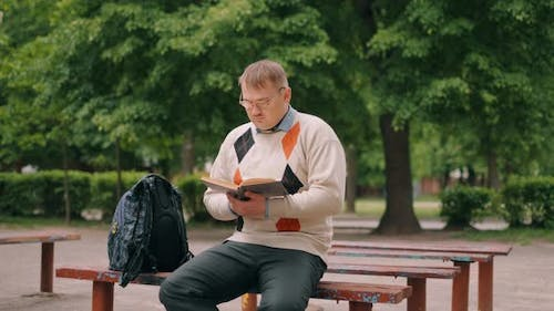 A Funny Nerdy Man Is Reading Book Outdoor. A Bookworm Loser with Glasses Is Preparing To Exam.