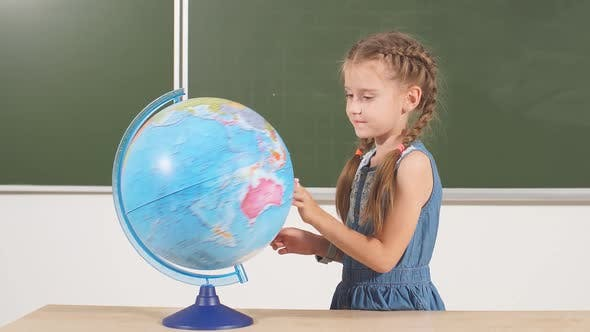 School Girl with Globe in Classroom Chalkboard on Background