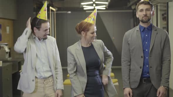 Thumbnail for Cheerful Caucasian Redhead Woman Standing with Two Male Colleagues in Open Space Office and Looking