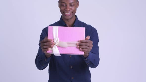 Young Happy African Businessman Giving Gift Box