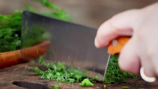 Man's Hand with a Large Knife Cut the Fresh Dill.