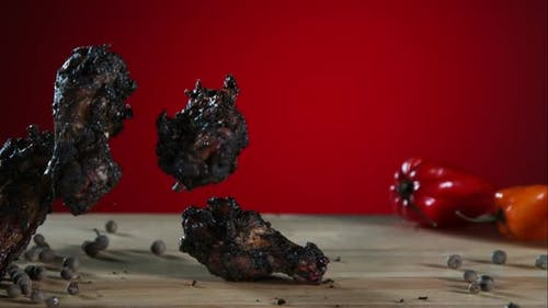 Smoked chicken wings falling and bouncing in ultra slow motion