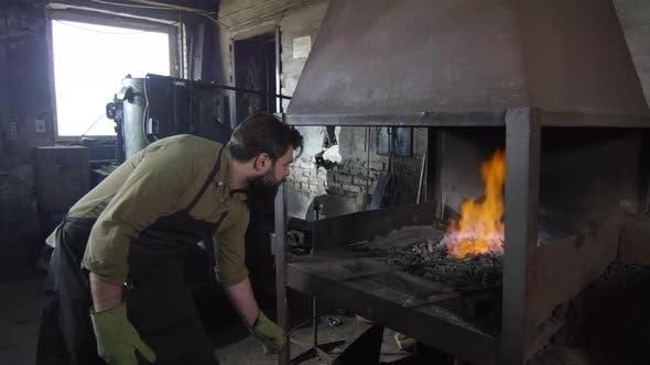 Thumbnail for Blacksmith Watching Billet Melting in Burning Coals
