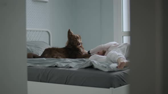 Girl and her pet friend cuddles on bed