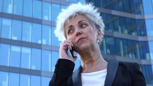 Thumbnail for A Middle-aged Businesswoman Talks on a Smartphone in an Urban Area - a Windowed Office Building
