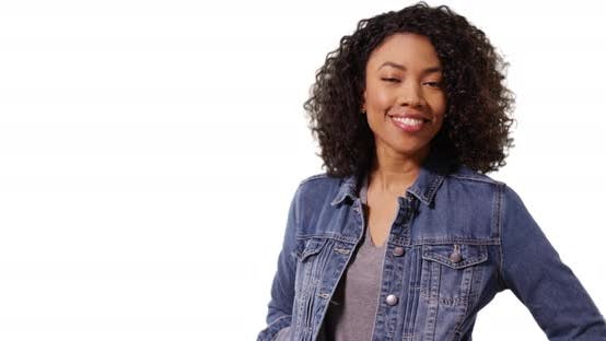 Cute African female with curly hair smiling at camera cheerfully in studio