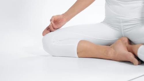 Unrecognizable Woman in White Space Practice Yoga Sits in Lotus Position with Hands on Knees