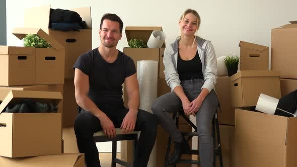 Thumbnail for A Happy Moving Couple Sits on Chairs in an Empty Apartment and Nods at the Camera with a Smile