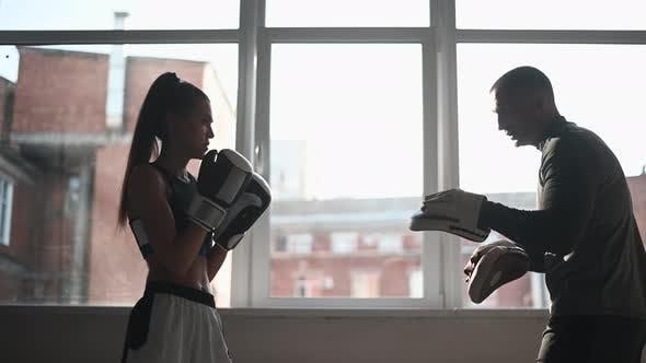 Thumbnail for Ein junges Mädchen führt Kickbox-Training durch und übt Pfotenschläge mit einem professionellen Boxer