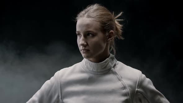 Thumbnail for A Young Pretty Woman Fencer in the Smoky Studio
