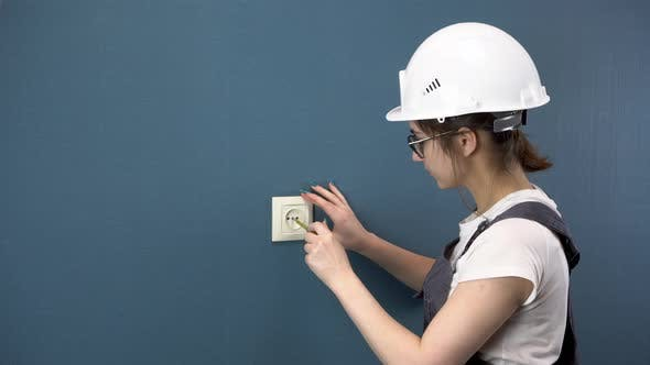An Electrician Repairs an Outlet in the House