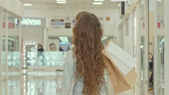 Thumbnail for Rear View Shot of a Curly Haired Little Girl Looking at Clothing Stores at Shopping Mall