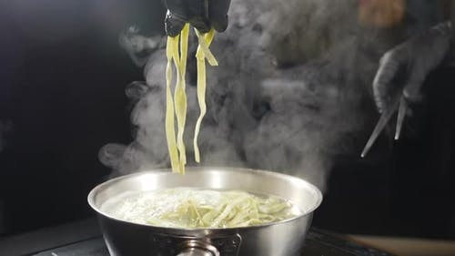 Chef in Black Gloves Putting Raw Pasta Into Boiling Water. White Smoke in Slow Motion Rising Above